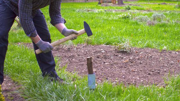 Bodenhülse in die Erde schlagen