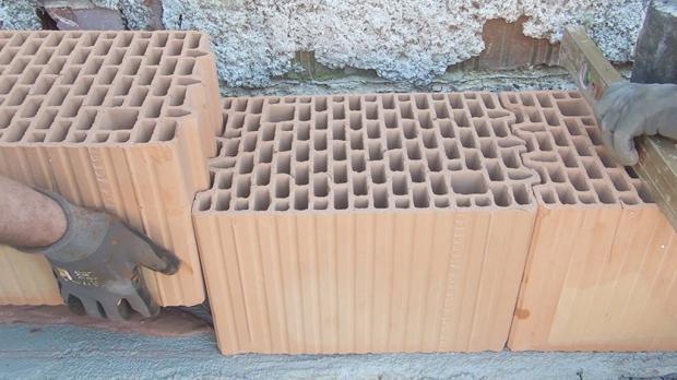 Mauern der Wand - Ziegel zwischen den Ecken versetzen