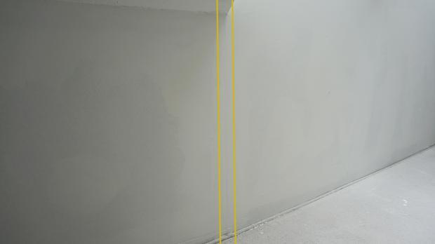 Helles Licht und die weiße Wand zeigen alle vorhandenen Unebenheiten
