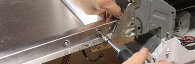 Schraube des rechten Geschirrspüler-Scharniers wird ausgeschraubt