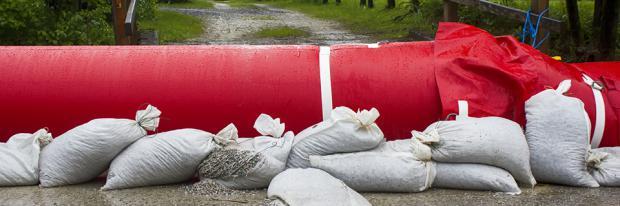 Wassergefülltes Hochwasser-System vor einer Brücke