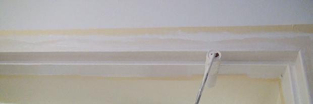 Farbwalze streicht den Türrahmen